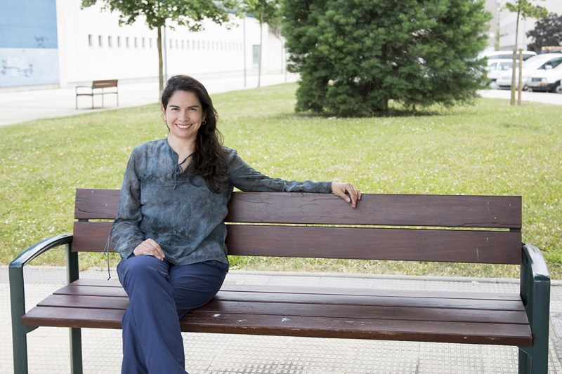 Foto de Marcela Vega sentada en un banco de madera