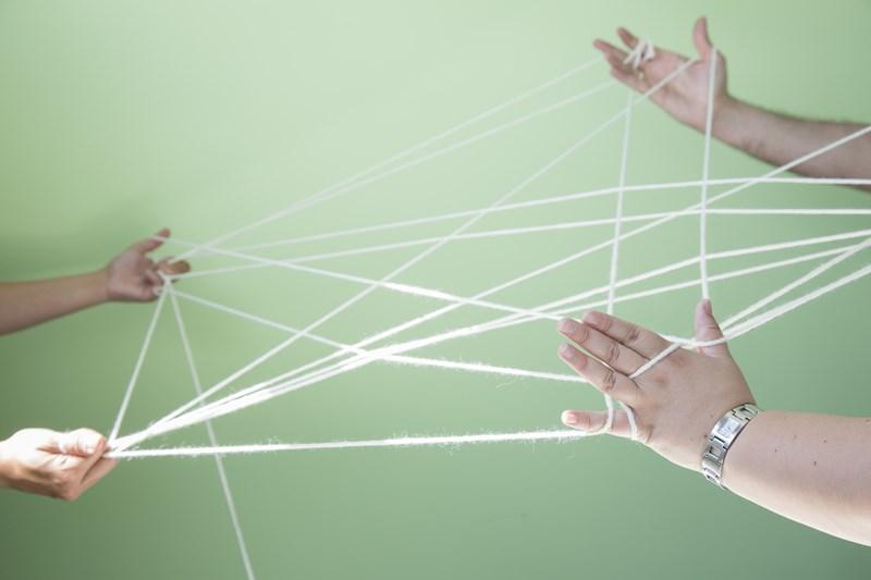 Foto de tres personas haciendo una red con un ovillo de lana