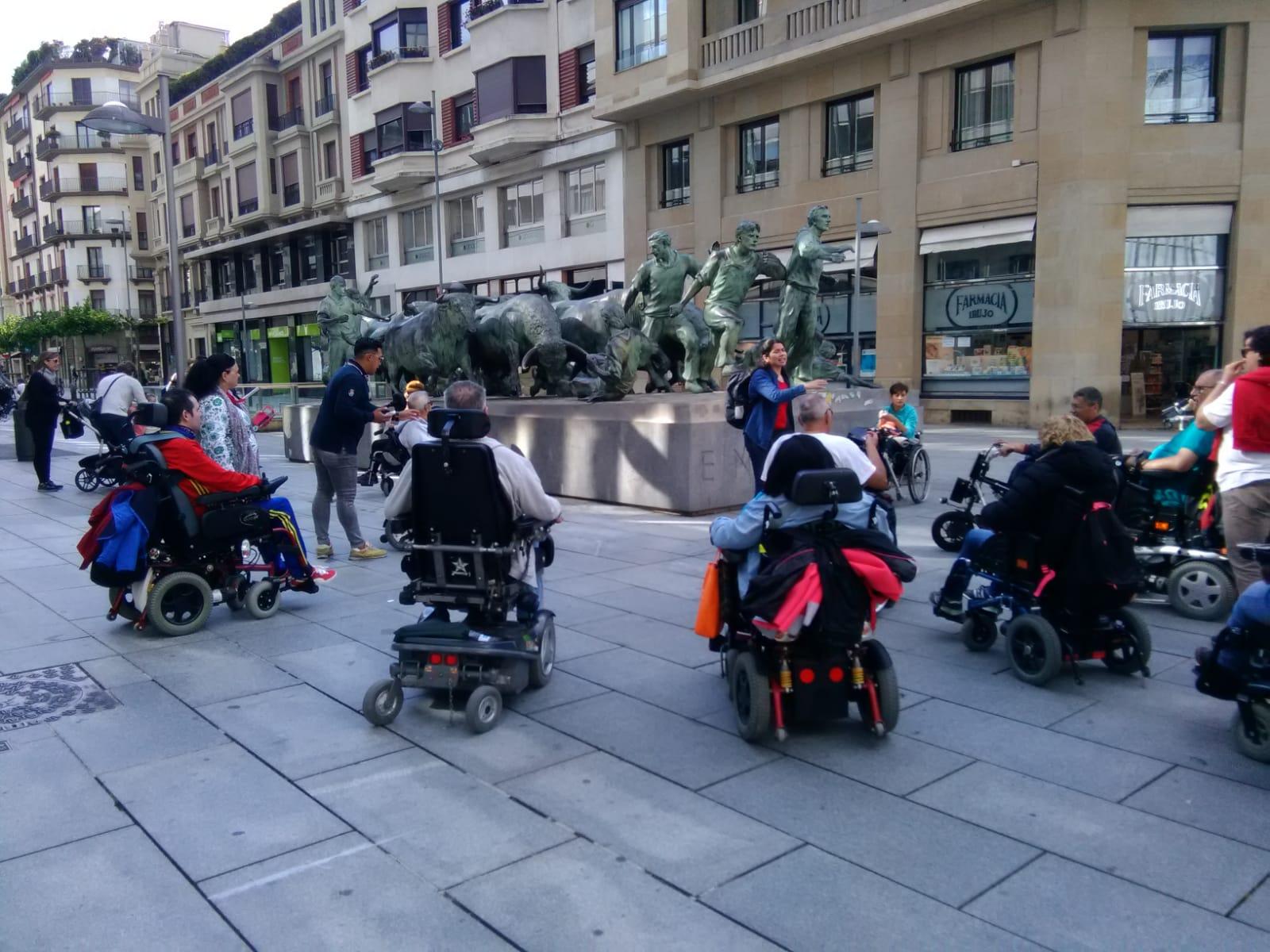 Visita accesible a Pamplona. Grupo de personas en silla de ruedas observando el Monumento al Encierro.