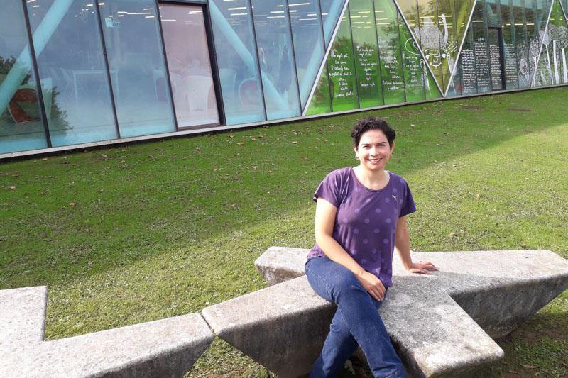 Foto de Marcela Vega sentada en un banco de piedra