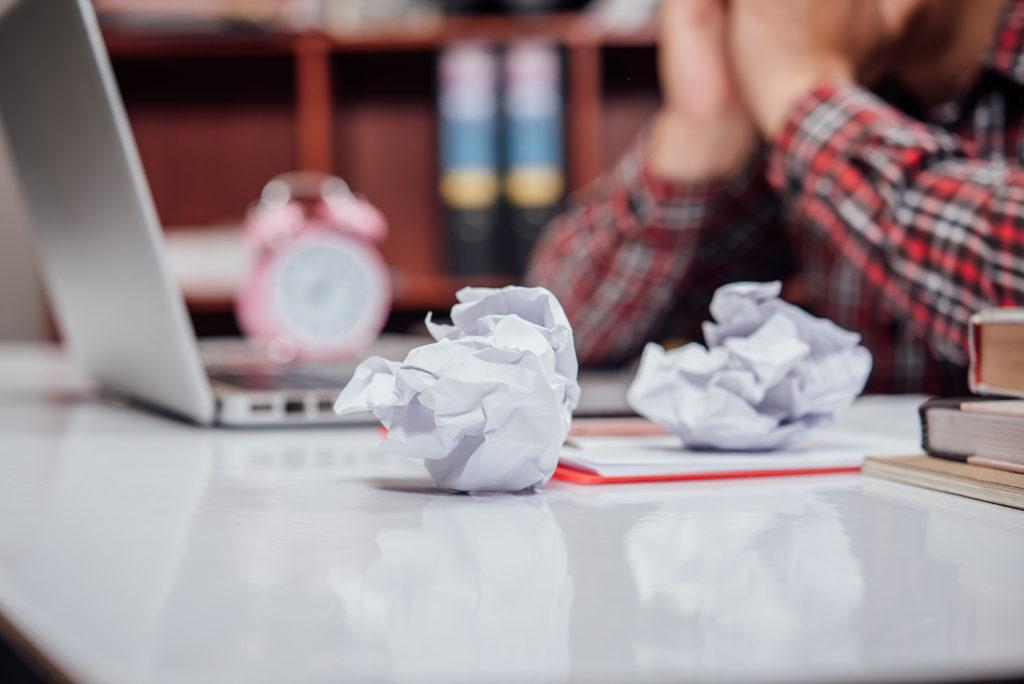 En primer plano unos papeles arrugados, al fondo una persona frente a un ordenador portátil con un gesto de frustración.