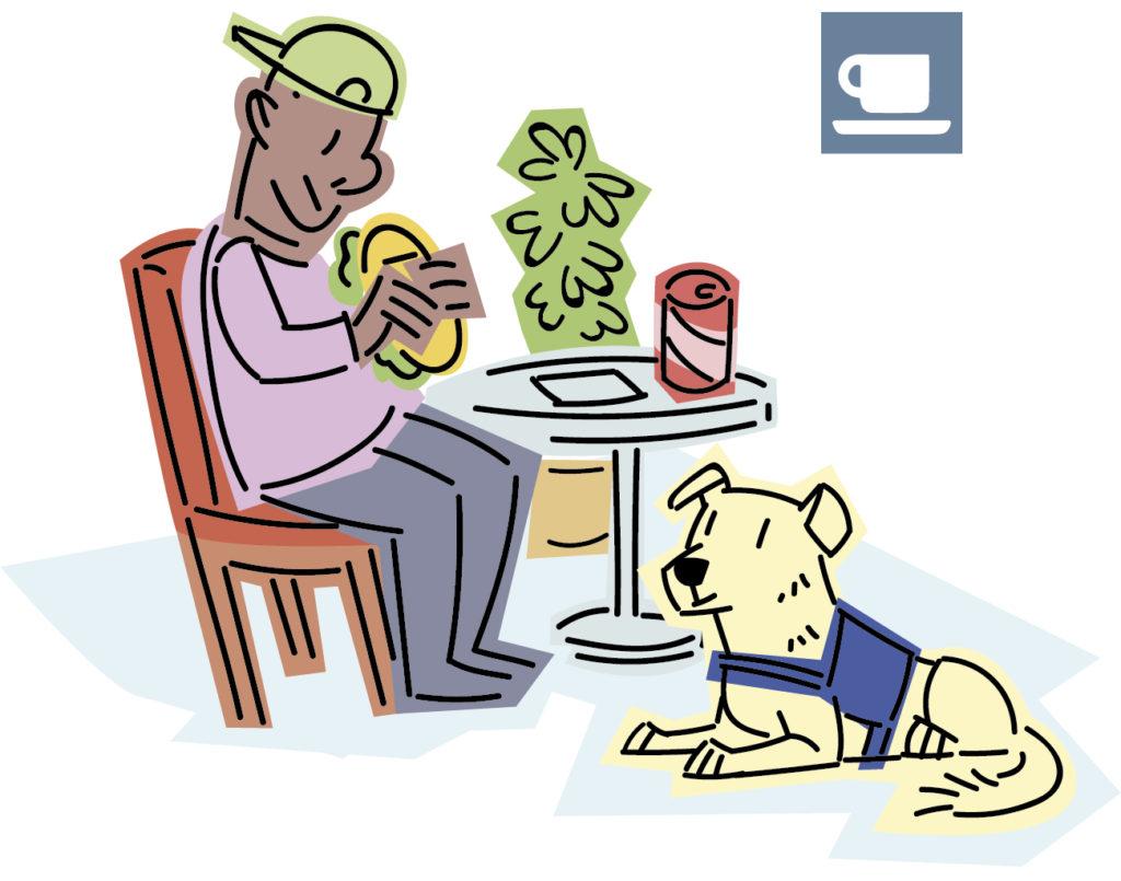 Chico comiendo un sánduche en una cafetería con su perro de asistencia a sus pies.