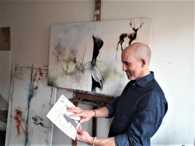 """El artista Fermín Alvira frente al cuadro """"El espacio infinito de los poetas"""", mientras observa una lámina táctil."""